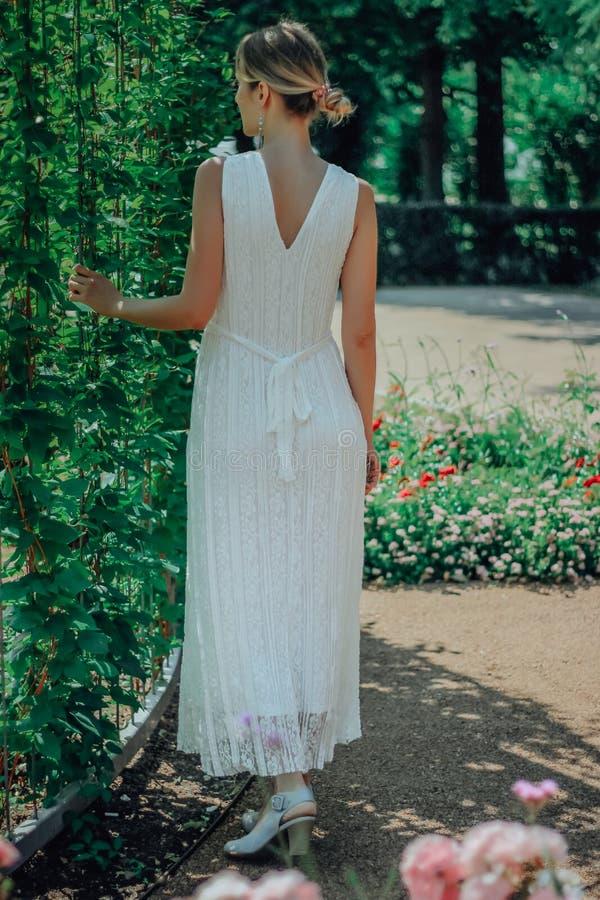Молодая красивая женщина в белом платье в зеленом саде с цветками закрывает вверх в summertimerr стоковые фото