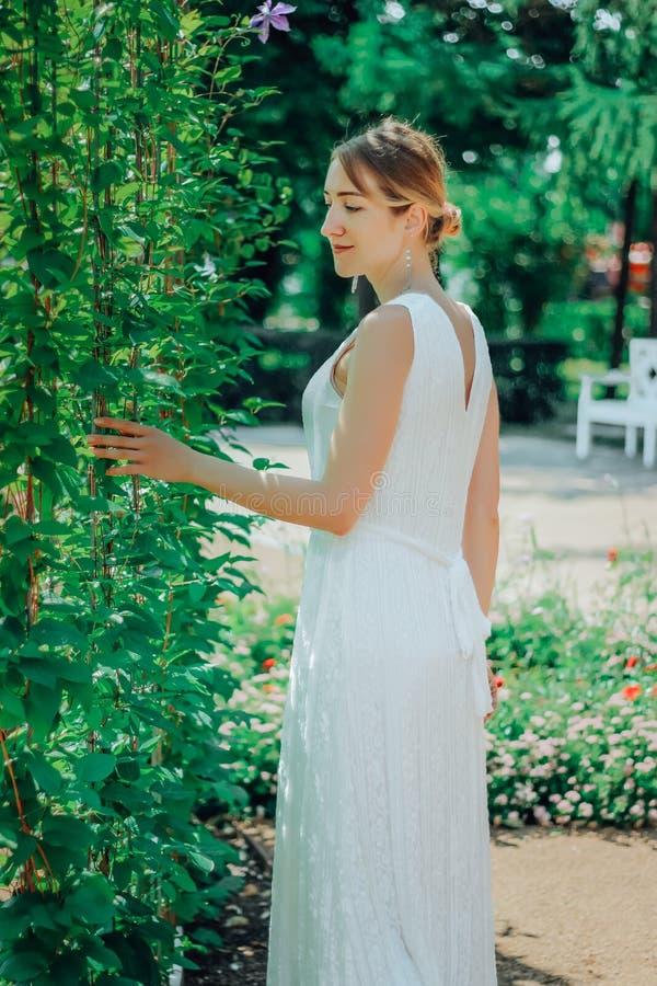 Молодая красивая женщина в белом платье в зеленом саде с цветками закрывает вверх в summertimerr стоковая фотография