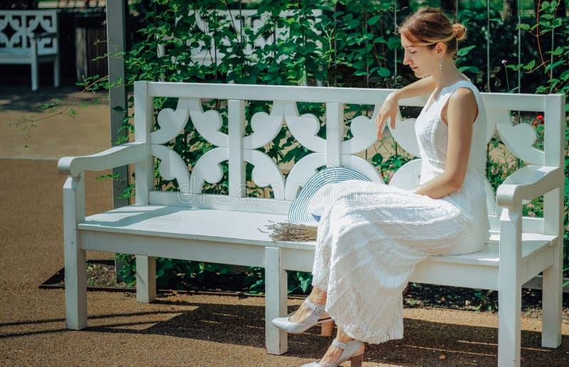 Молодая красивая женщина в белом платье в зеленом саде с цветками закрывает вверх в summertimerr стоковое фото