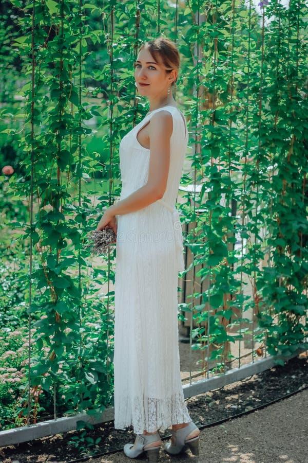 Молодая красивая женщина в белом платье в зеленом саде с цветками закрывает вверх в summertimerr стоковая фотография rf