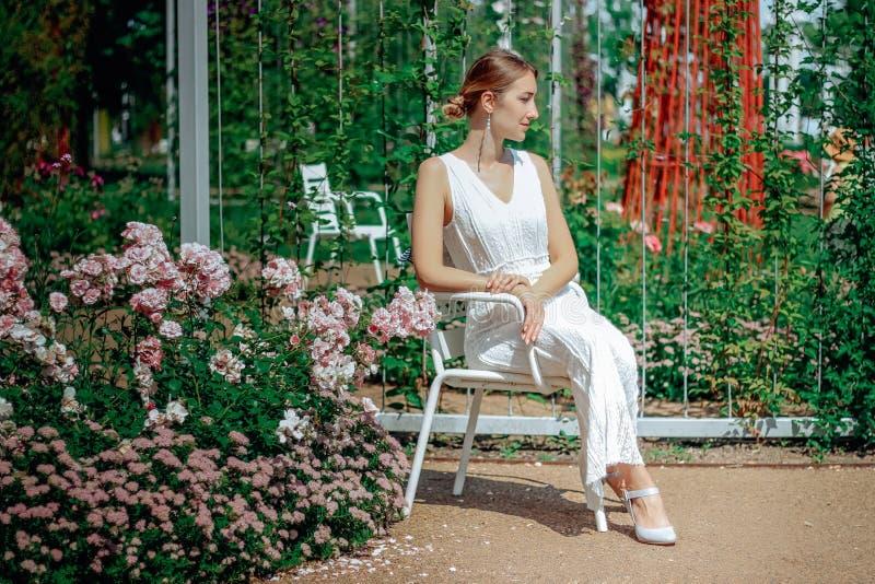 Молодая красивая женщина в белом платье в зеленом саде с цветками закрывает вверх в summertimerr стоковое фото rf