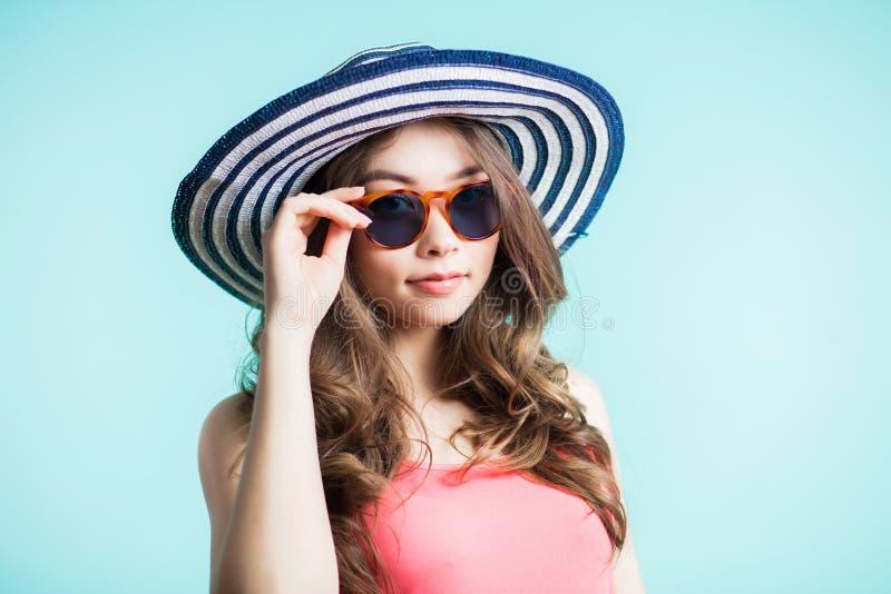 Молодая красивая женщина в бикини, шляпе и солнечных очках стоя на пляже Летние отпуска и концепция каникул стоковое изображение rf