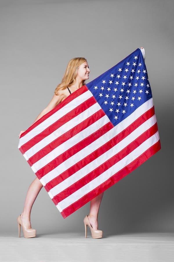 Молодая красивая женщина в красном женское бельё держа американский флаг стоковая фотография