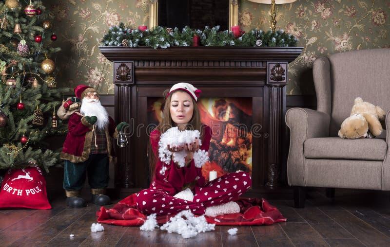 Молодая красивая женщина в красных пижамах одежд дома рождества сидит под рождественской елкой около камина и дует искусственный стоковая фотография