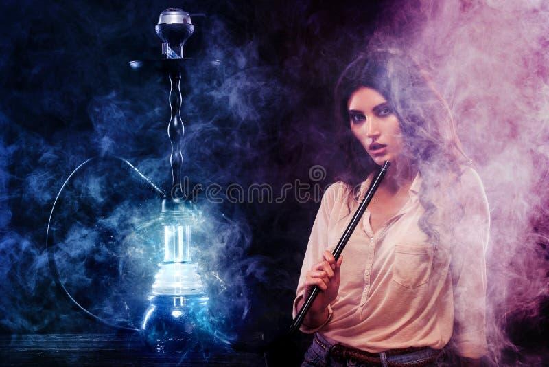 Молодая, красивая женщина в ночном клубе или дым бара кальян Удовольствие курить Сексуальный дым стоковое изображение