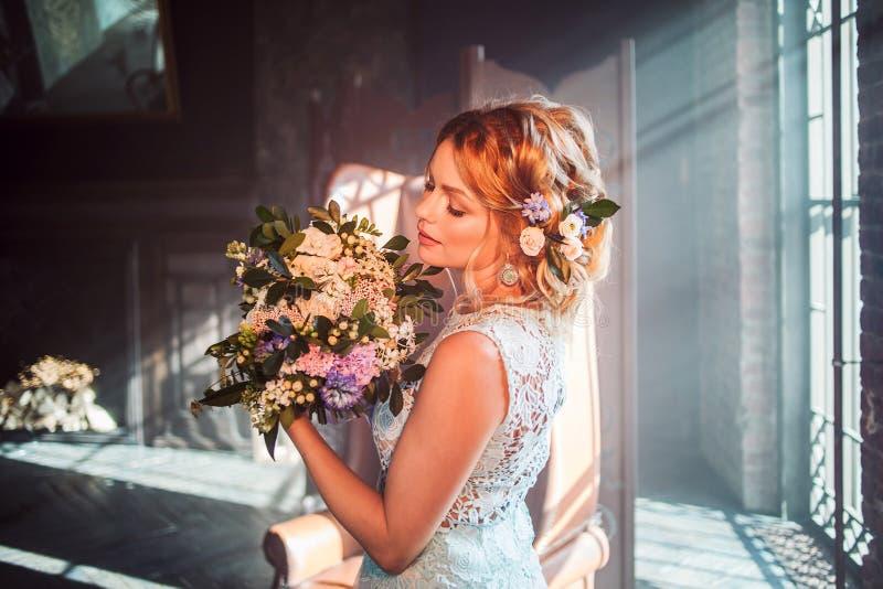 Молодая красивая женщина в платье свадьбы с букетом цветков Стиль причёсок свадьбы, цветки в волосах стоковые фото