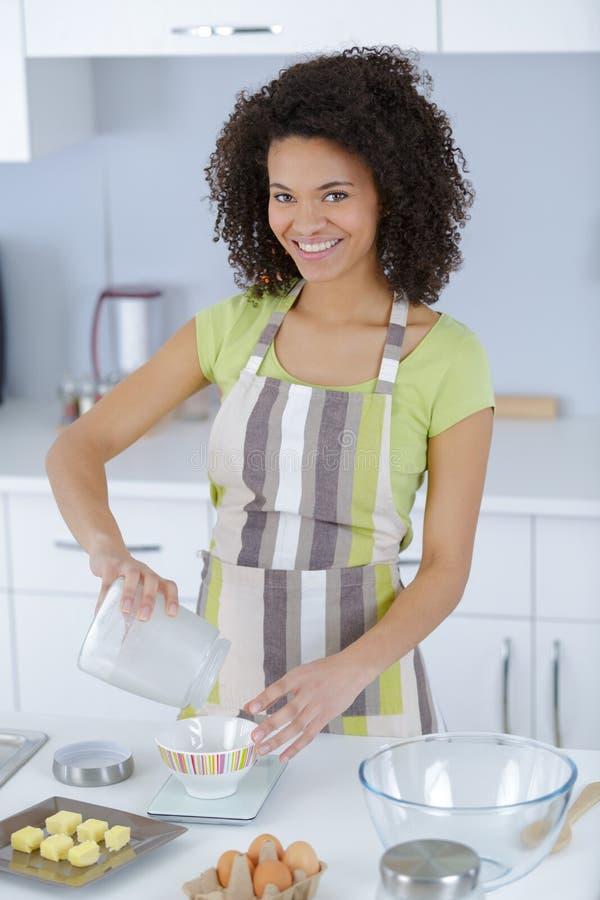 Молодая красивая женщина в рисберме делая торт стоковые изображения rf