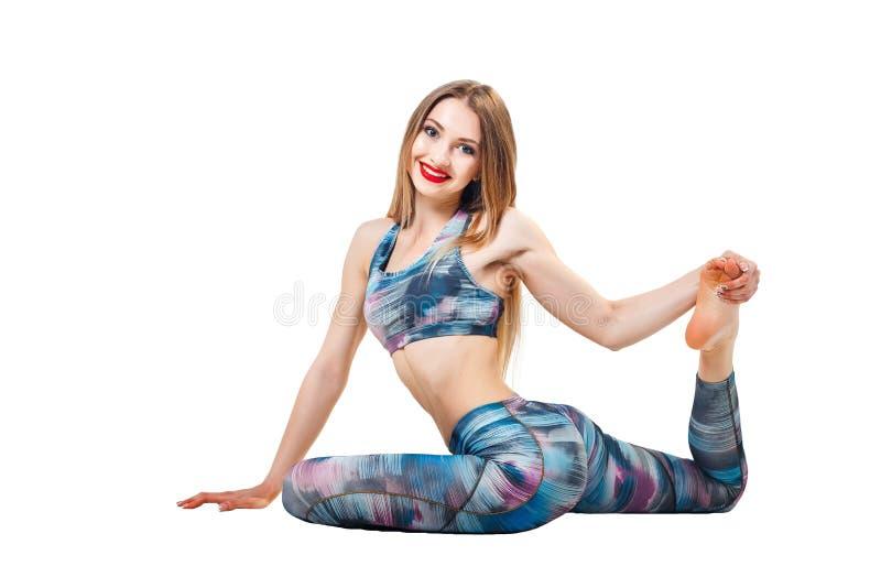 Молодая красивая женщина в цвет-голубой представлять йоги верхней части и гетры изолированная над белой предпосылкой студии и смо стоковые фотографии rf