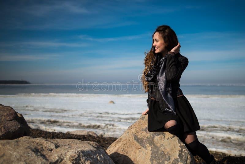 Молодая красивая женщина в элегантных одеждах с шарфом сидит на береговой линии в сезоне и смотреть зимы прочь стоковое фото