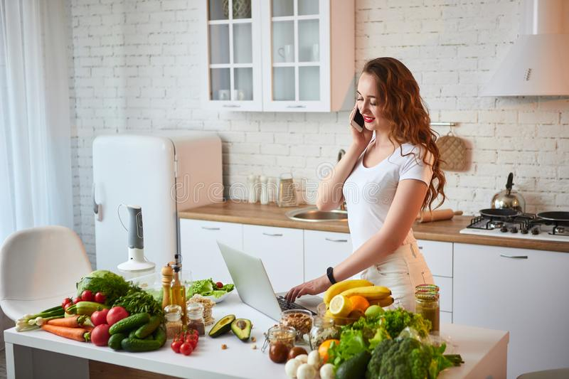 Молодая красивая женщина говоря на смартфоне и используя тетрадь пока варящ в современной кухне Здоровая еда и Dieting стоковое фото rf