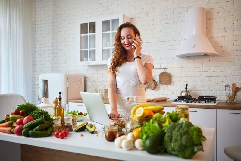 Молодая красивая женщина говоря на смартфоне и используя тетрадь пока варящ в современной кухне Здоровая еда и Dieting стоковое изображение rf