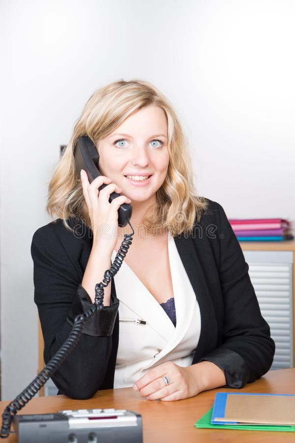 Молодая красивая женщина говоря на телефоне и смотря камеру с улыбкой пока сидящ на ее месте службы стоковые фото