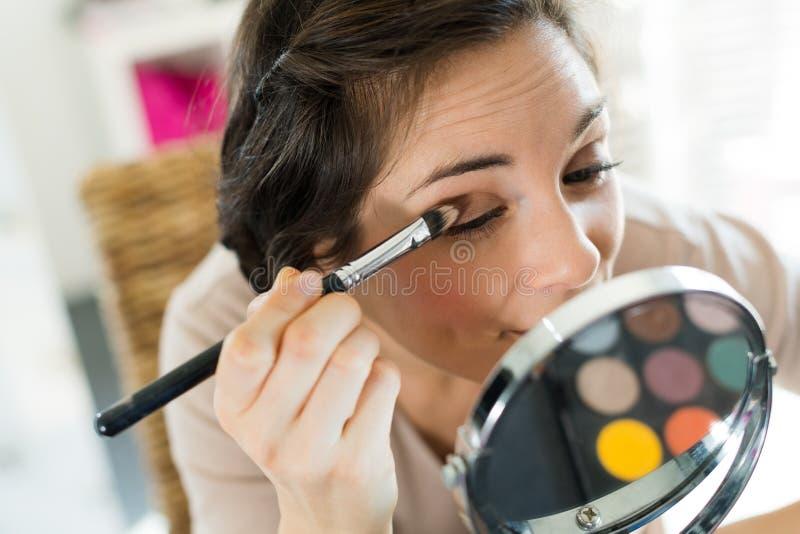Молодая красивая женщина делая макияж около зеркала стоковое изображение