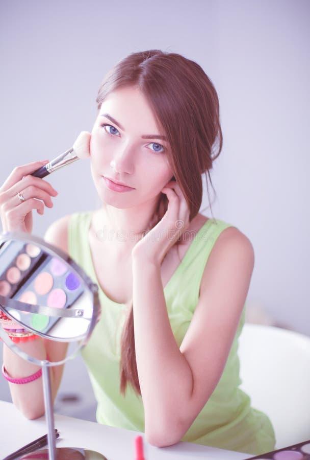 Молодая красивая женщина делая макияж около зеркала, сидя на столе стоковое изображение