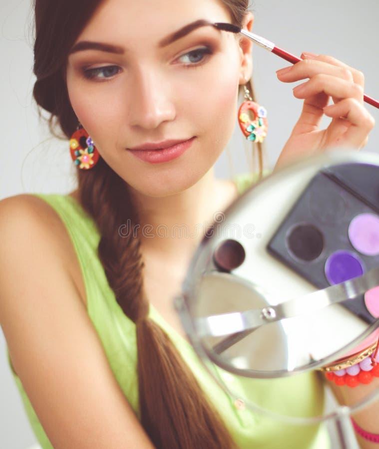 Молодая красивая женщина делая макияж около зеркала, сидя на столе стоковое фото