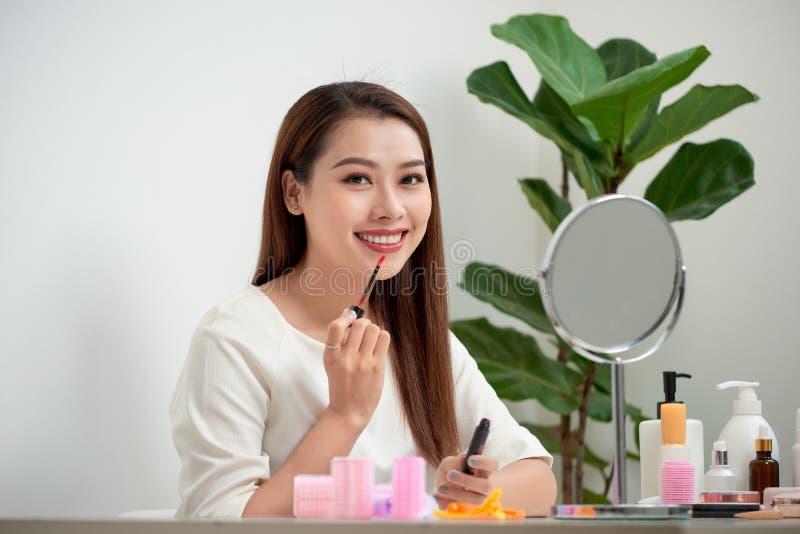 Молодая красивая женщина делая состав около зеркала стоковое изображение rf