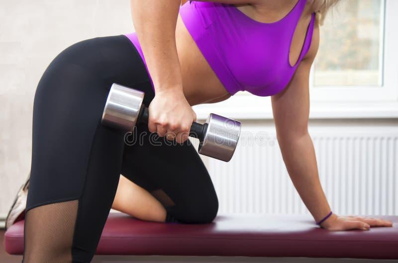 Молодая красивая женщина делая тренировки с гантелью в спортзале Радостная усмехаясь девушка наслаждается с ее процессом трениров стоковое изображение rf