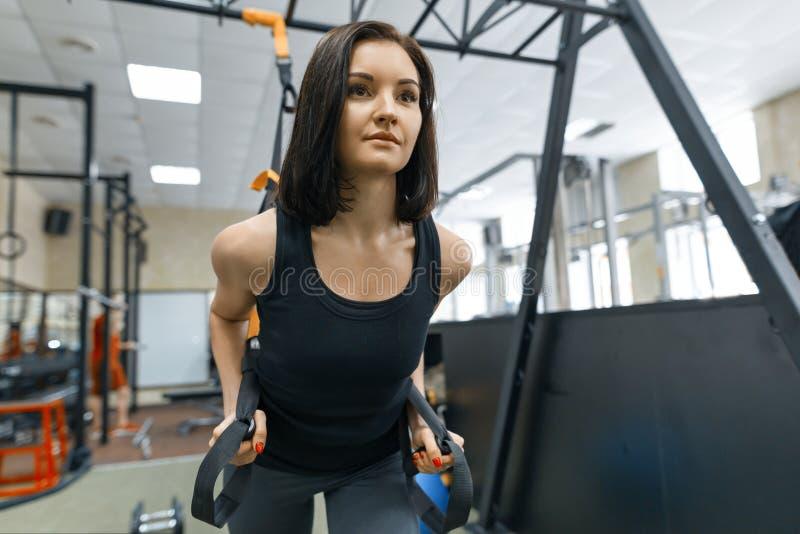 Молодая красивая женщина делая crossfit с ремнями фитнеса trx в спортзале Спорт, фитнес, тренировка, концепция людей стоковая фотография