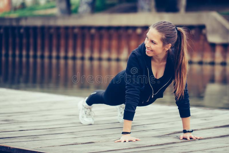 Молодая красивая женщина делая outdoors нажима вверх стоковое изображение rf