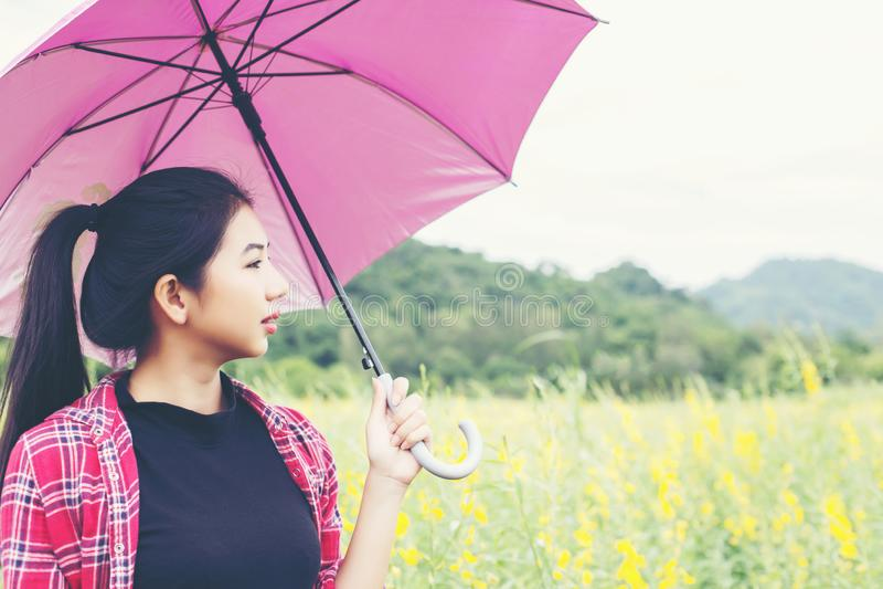 Молодая красивая женщина держа красный зонтик в желтых поле цветка и предпосылке горы стоковая фотография