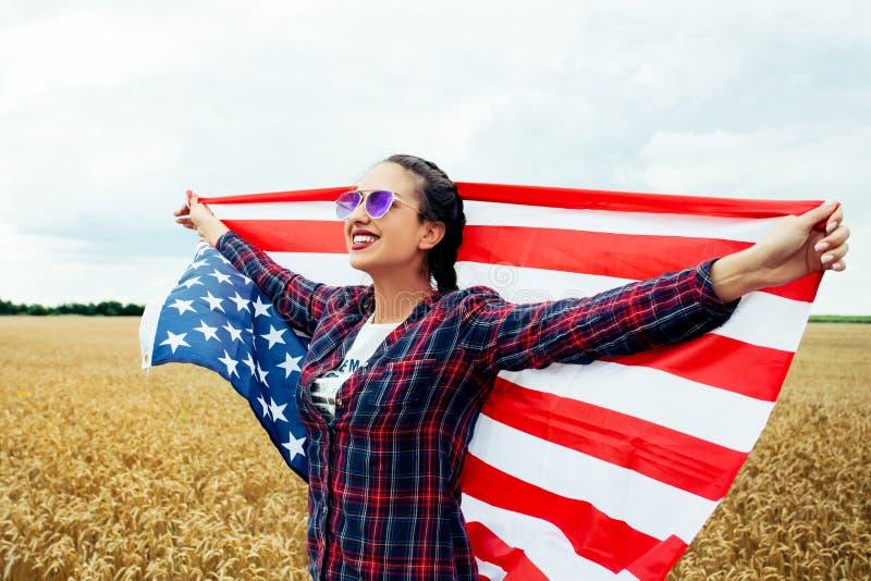Молодая красивая женщина держа флаг США стоковая фотография rf
