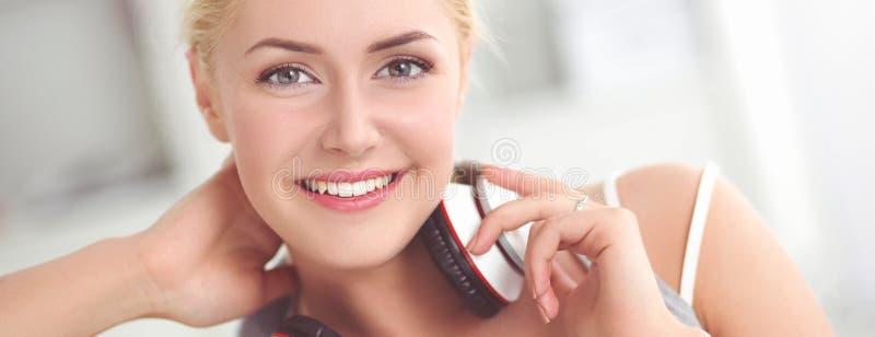 Молодая красивая женщина дома сидя на софе и слушая музыке стоковые изображения
