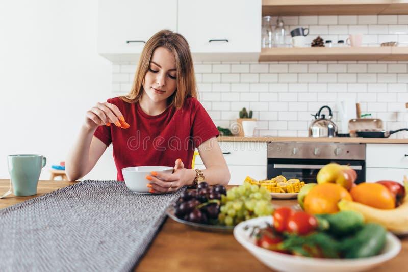 Молодая красивая женщина есть еду фруктов и овощей здоровую в кухне стоковое фото