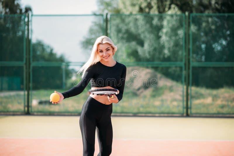 Молодая красивая женщина играя теннис на суде Здоровый образ жизни спорта стоковое изображение