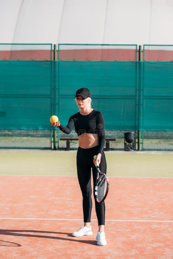 Молодая красивая женщина играя теннис на суде Здоровый образ жизни спорта стоковое фото