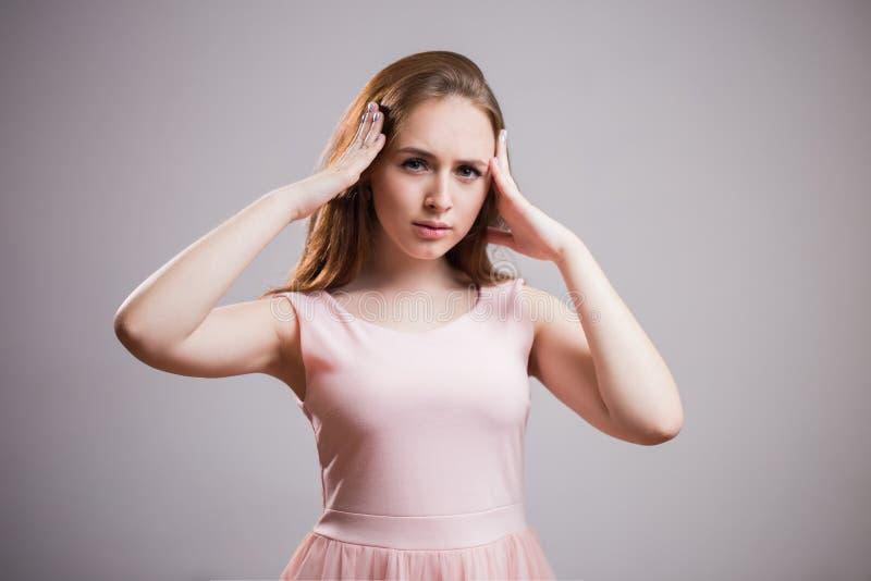 Молодая красивая женщина имеет головную боль, изолированную на серой предпосылке стоковое фото