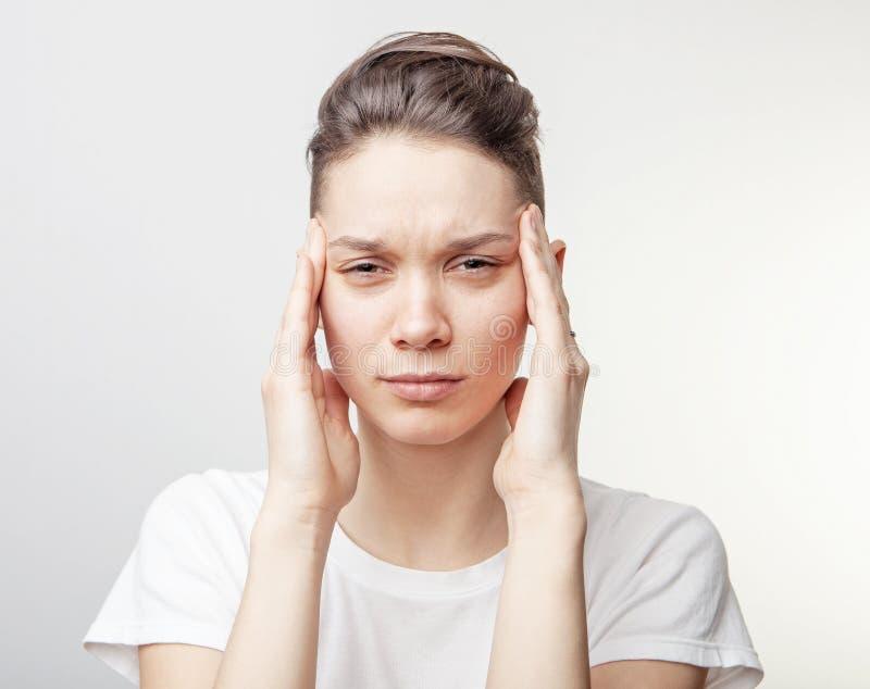 Молодая красивая женщина имеет головную боль, изолированную на серой предпосылке стоковое фото rf