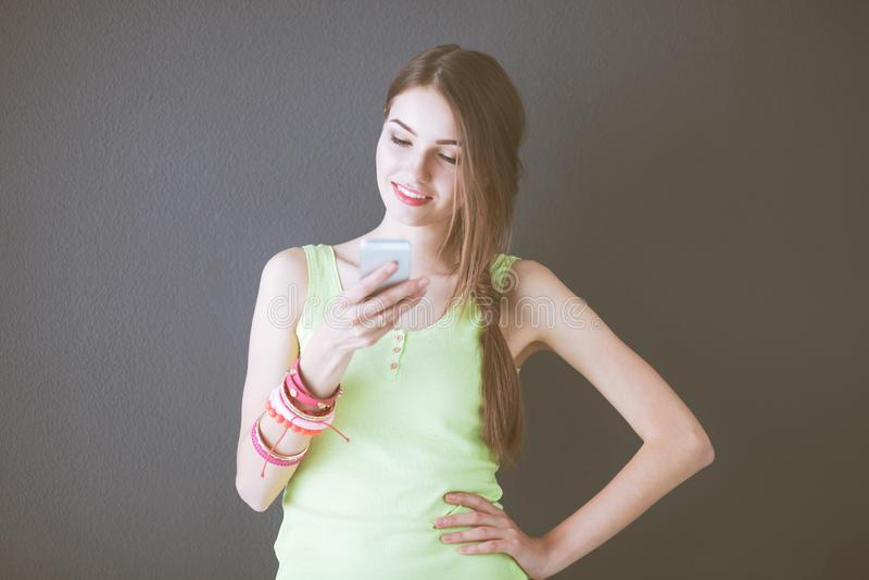 Молодая красивая женщина используя предпосылку изолированную смартфоном серую стоковое фото rf