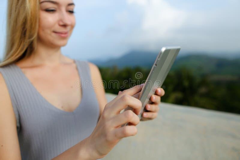 Молодая красивая женщина используя таблетку в предпосылке гор стоковое изображение rf