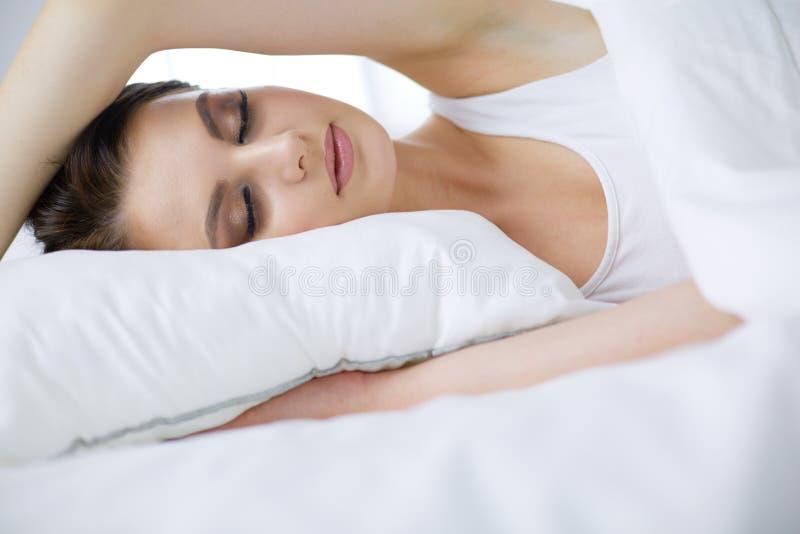 Молодая красивая женщина лежа в кровати стоковые фотографии rf