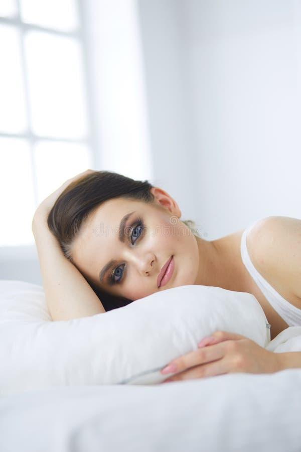 Молодая красивая женщина лежа в кровати стоковое фото