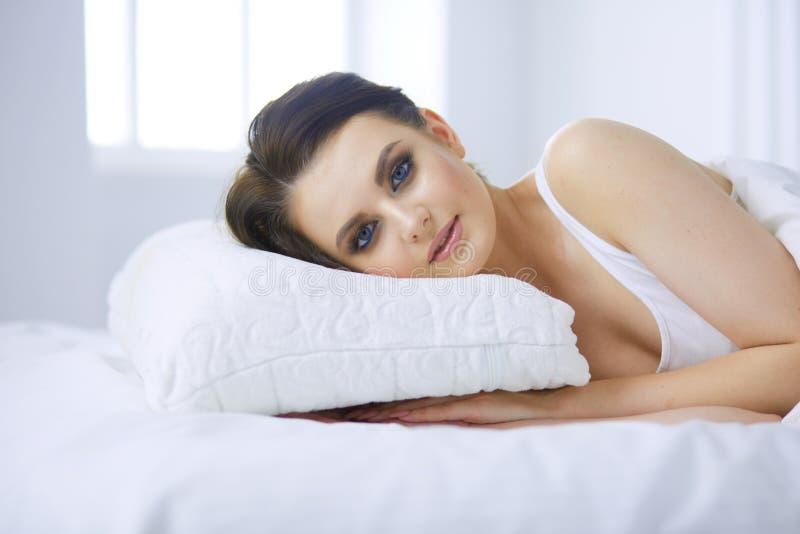 Молодая красивая женщина лежа в кровати стоковые изображения rf
