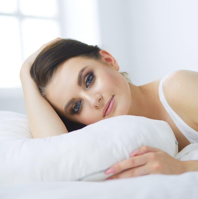 Молодая красивая женщина лежа в кровати стоковые фото