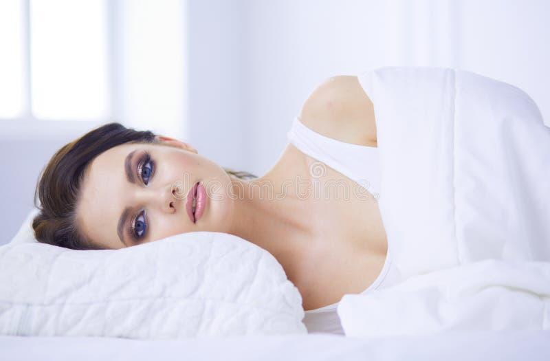Молодая красивая женщина лежа в кровати стоковое изображение rf