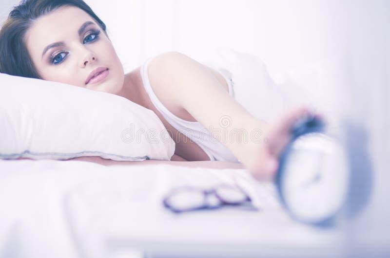 Молодая красивая женщина лежа в кровати стоковая фотография