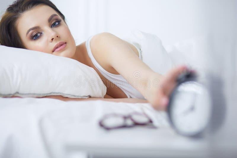 Молодая красивая женщина лежа в кровати стоковая фотография rf