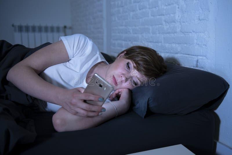 Молодая красивая женщина лежа в падать кровати уснувший используя умный телефон поздно на ноче в темной спальне стоковые изображения rf