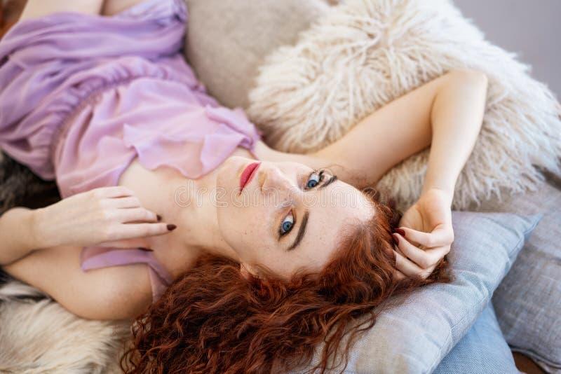 Молодая красивая женщина лежа на кровати, красивых красных волосах, релаксации и концепции релаксации стоковое фото rf