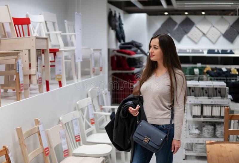 Молодая красивая женщина находя новая мебель, деревянные стулья стоковые изображения rf