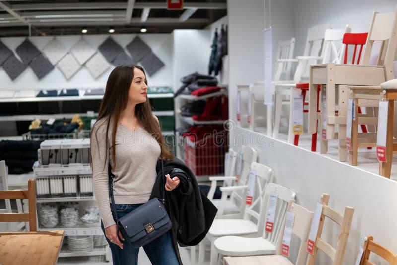 Молодая красивая женщина находя новая мебель, деревянные стулья стоковые изображения