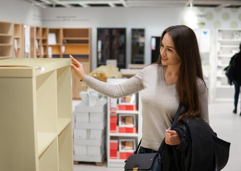 Молодая красивая женщина находя новая мебель, украшение стоковые фотографии rf