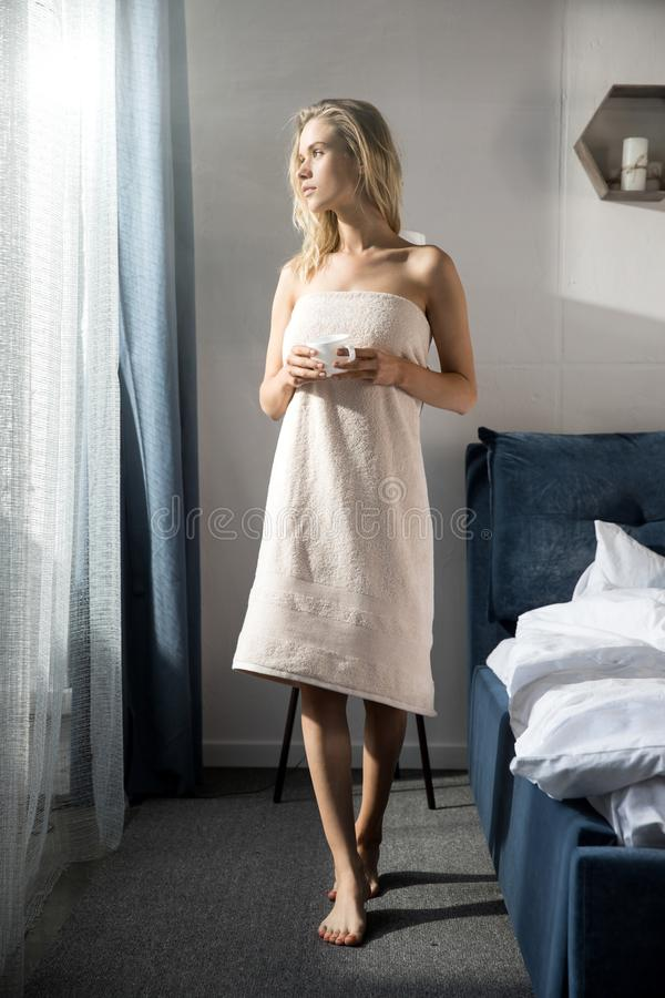 Молодая красивая женщина обернутая вверх при полотенце ванны стоя с кофе стоковое изображение