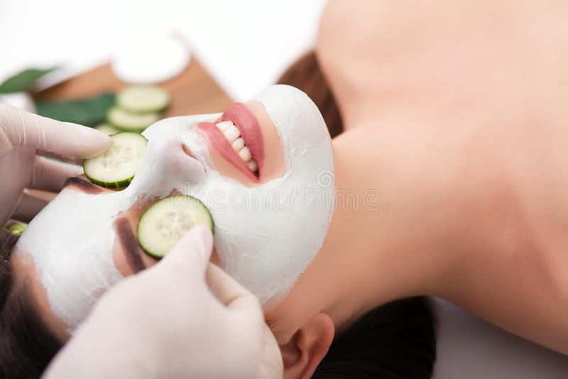Молодая красивая женщина получая маску глины лицевую в салоне красоты курорта Забота кожи, косметики стоковые изображения