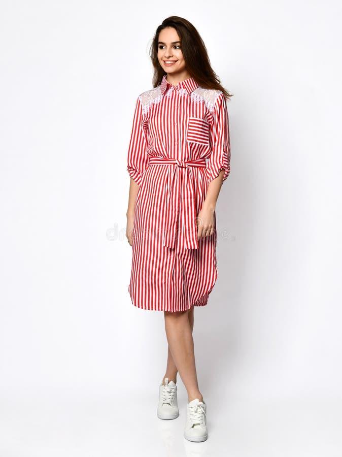 Молодая красивая женщина представляя в новом розовом красном платье моды нашивок на теле высоких холмов полном на белом стоковое изображение