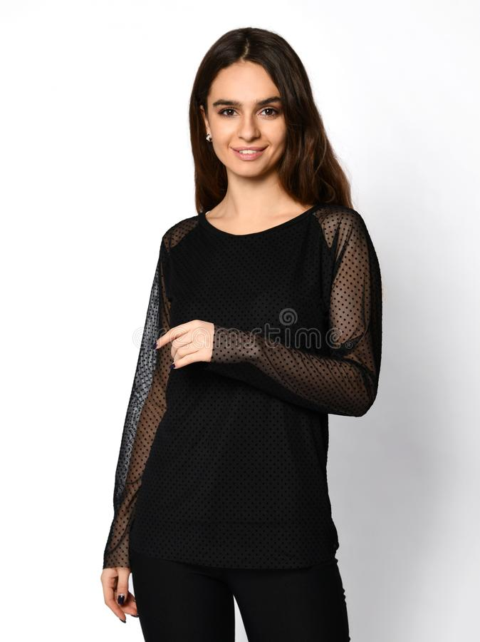 Молодая красивая женщина представляя в рубашке блузки новой моды случайной темной с рукавами сделанными из просвечивающей ткани и стоковая фотография