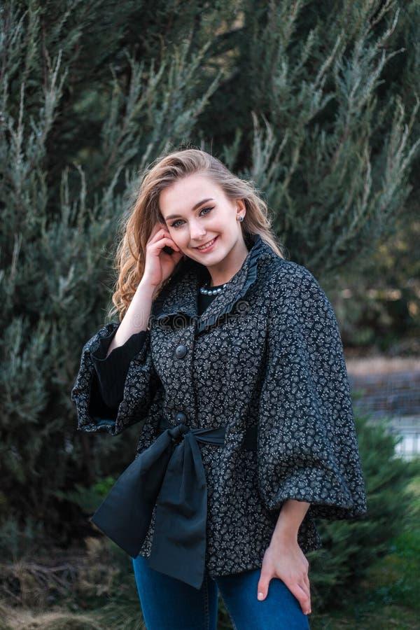 Молодая красивая женщина представляя на камере outdoors стоковая фотография